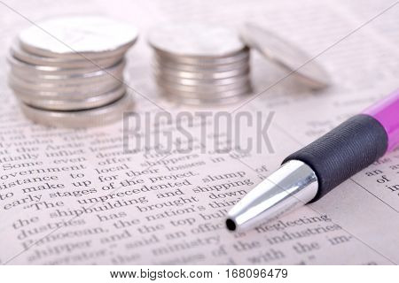 Ballpoint pens and coins placed on newspaper articles