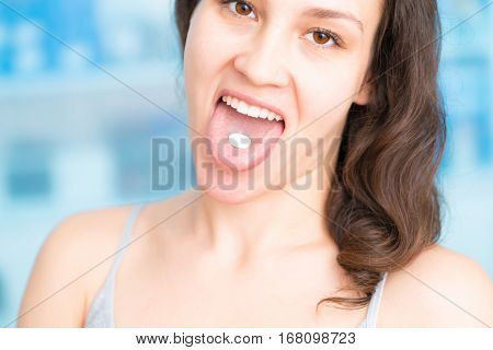 Young woman takes a pill. Cute young woman sticking her tongue out with pill on it