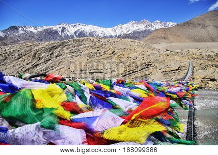 Suspension bridge between Lower Mustang and Upper Mustang with lot of colorful buddhist praying flags