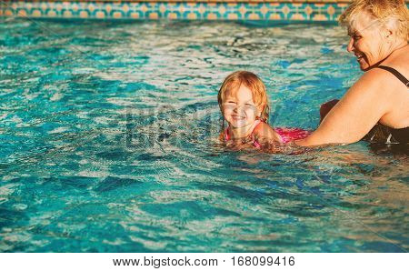 grandmother teaching little granddaughter to swim, active retirement
