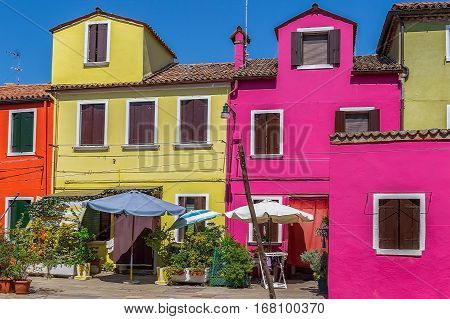 BURANO ITALY - AUGUST 5 2015: Colorful houses in Burano Italy an island with colorful architecture in the Venetian Lagoon.