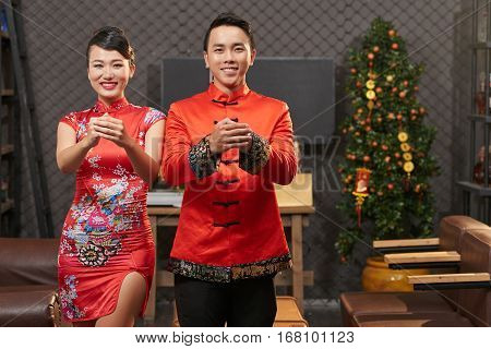 Smiling Asian couple making gesture to wish you happy New Year