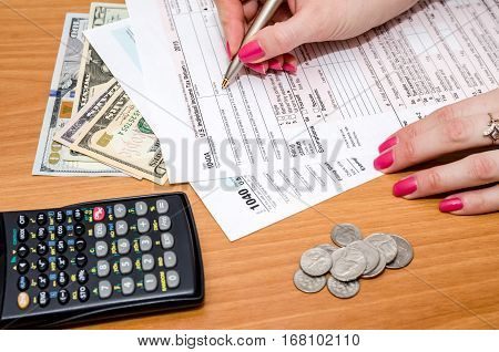 Person filing 1040 tax form on desk