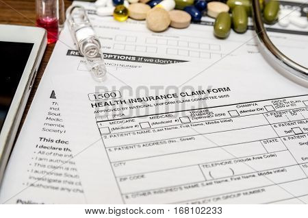 personal health insurance claim form with pills syringe mobile phone stethoscope