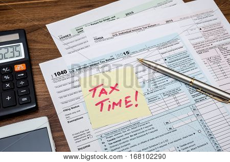 Tax time word on tax form with calculator pen glasses