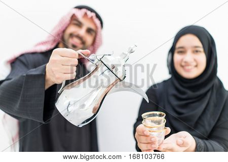 Gulf Arabian young couple with traditional welcome hospitality coffee