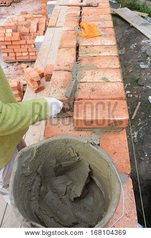 Bricklaying. Bricklayer worker installing red brick wall with trowel putty knife outdoor. Basic Bricklaying.