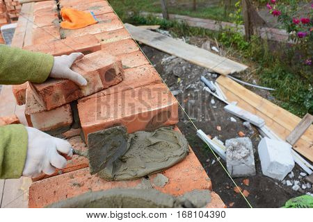 Bricklaying. Bricklayer worker installing red blocks and caulking brick masonry joints exterior brick house wall with trowel putty knife outdoor. Basic Bricklaying.