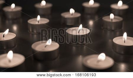 Flame of many candles burning on the background in brown and sepia color - saddness