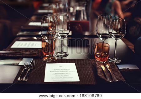 Set the table for tasting wine and dish. Table in the restaurant with table appointments - glasses, forks and knives. Menu there and blurred background