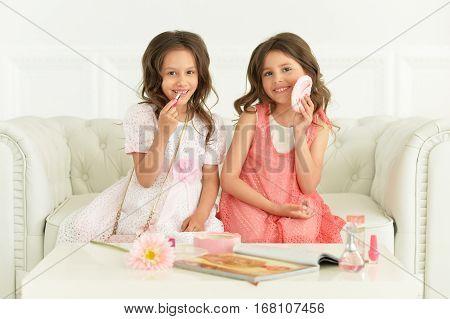 two little girls reading magazine using cosmetics