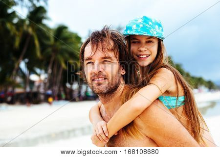 Dad playing with his 10 years old daughter on the tropical beach