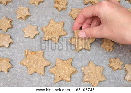 Female Hand Take Cutted Christmas Cookies From Rye Dough With Star Shaped Cutter