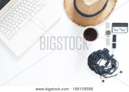 Overhead view of computer laptop a cup of coffee and woman accessories on white background with copy space