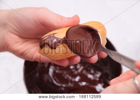 Eclairs or profiterole with chocolate and whipped cream. Spreading chocolate on top of eclair with spoon. Pastry Eclair imposes on a layer of melted chocolate with a spoon