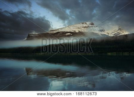 Snowcapped mountain and fog with lake reflection in Yoho National Park in Canada