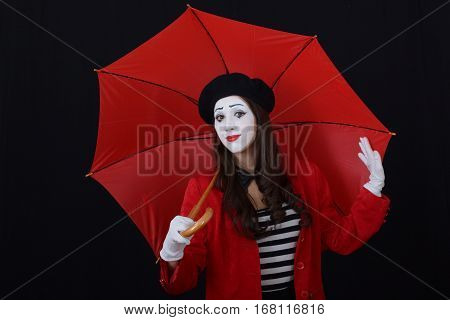 Girl in makeup mime standing under a red umbrella