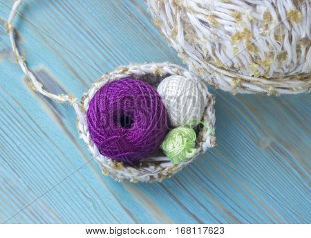 White green and violet small cotton yarn balls for knitting crochet on the wooden rustic background. Melange yarn