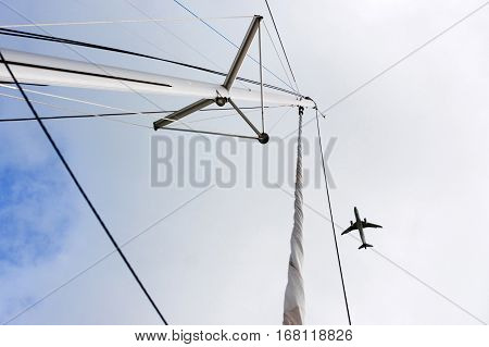 Plane over the mast. flying plane. Airplane and yacht