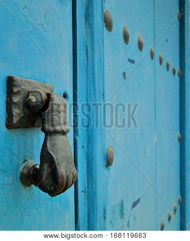 Blue wooden door with iron hand door knocker in Spain.