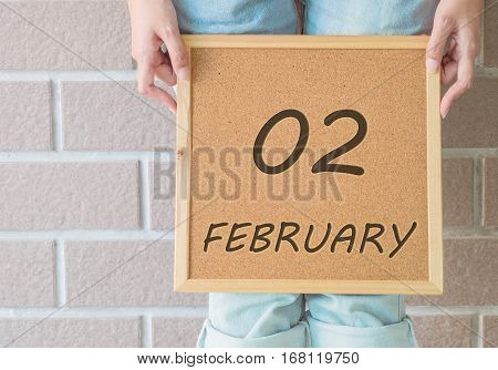 Closeup calendar at the cork board in hand of asian woman in front of her legs with 2 february word on brick wall textured background