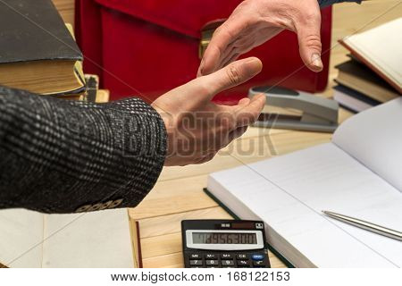 Business concept. Business partners handshaking after signing contract. Pertnership. On a wooden table books, documents, calculator, red briefcase