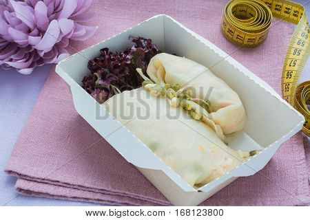 The stuffed cabbage in a craft box on a on a linen cloth with a centimetric tape. Healthy nutrition dish.