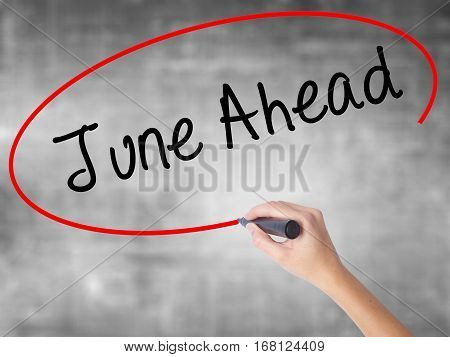 Woman Hand Writing June Ahead With Black Marker Over Transparent Board