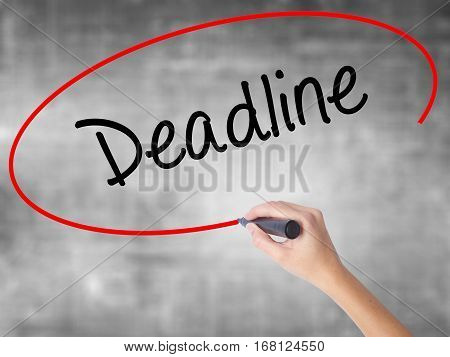 Woman Hand Writing Deadline With Black Marker Over Transparent Board