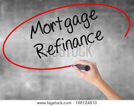 Woman Hand Writing Mortgage Refinance With Black Marker Over Transparent Board