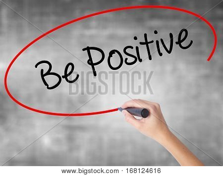 Woman Hand Writing Be Positive  With Black Marker Over Transparent Board