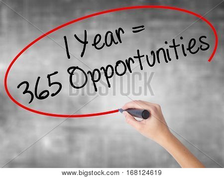 Woman Hand Writing 1 Year = 365 Opportunities With Black Marker Over Transparent Board