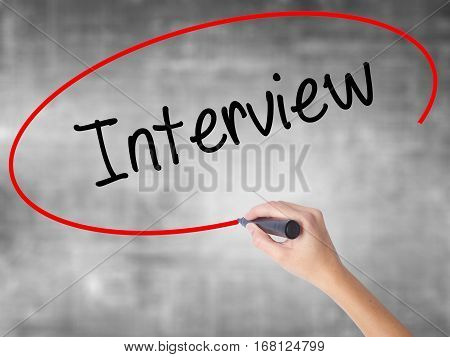 Woman Hand Writing Interview With Black Marker Over Transparent Board