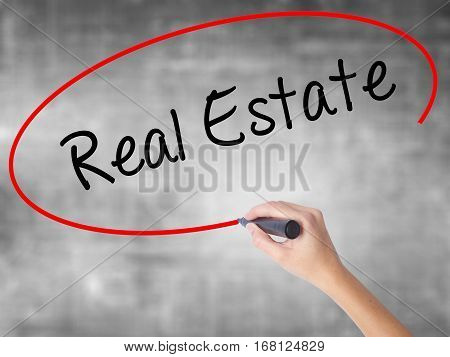 Woman Hand Writing Real Estate  With Black Marker Over Transparent Board