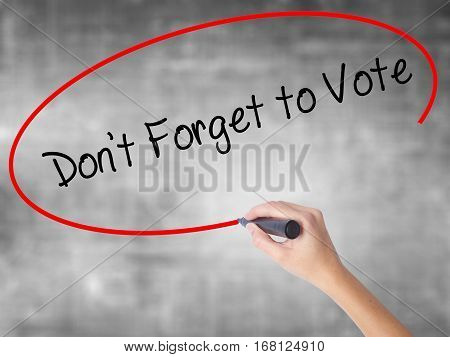 Woman Hand Writing Don't Forget To Vote With Black Marker Over Transparent Board