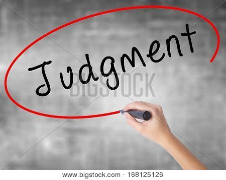 Woman Hand Writing Judgment With Black Marker Over Transparent Board
