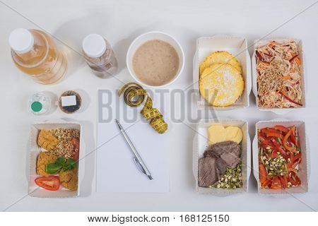Healthy nutrition plan. Fresh daily meals delivery. Restaurant food for one vegetable meat and fruits in foil boxes detox water business card notebook and pencil on white background. Fitness food.