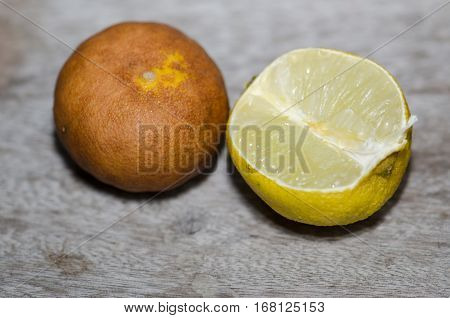 Lemon ripe withered unappetizing. Brown was placed on the wooden floor.