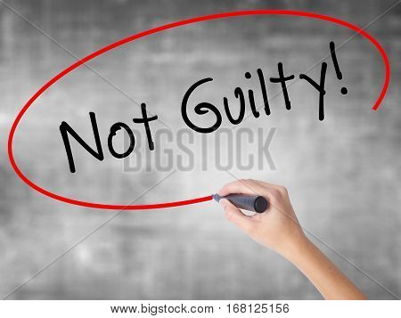 Woman Hand Writing Not Guilty With Black Marker Over Transparent Board