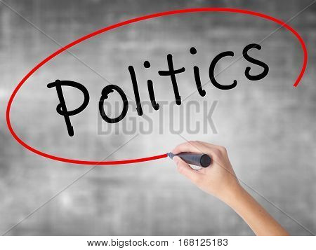 Woman Hand Writing Politics With Black Marker Over Transparent Board