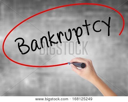Woman Hand Writing Bankruptcy With Black Marker Over Transparent Board