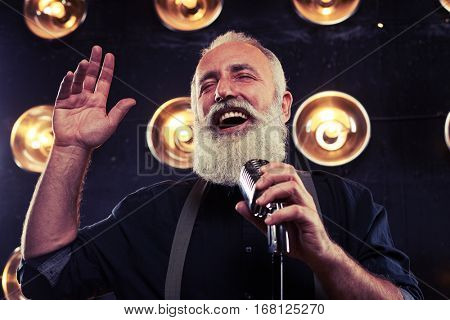 Close-up of happy and extremely pleased bearded man. Extremely pleased bearded man enjoying a jazz song isolated on the stage over spotlights