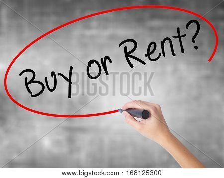 Woman Hand Writing Buy Or Rent? With Black Marker Over Transparent Board