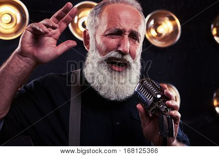 Close-up shot graceful bearded man in dark shirt and suspenders with hand up looking away from the camera. Good-looking man in official wear with a gray beard