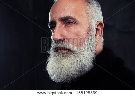 Indoors shot of stylish handsome adult man with gray long gray beard. Man looking aside. The concept of confidence and masculinity