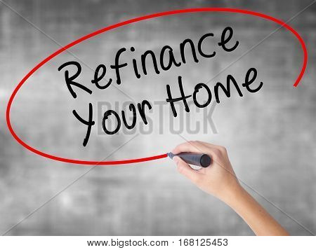 Woman Hand Writing Refinance Your Home With Black Marker Over Transparent Board