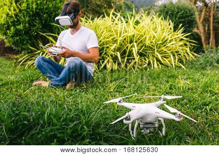 A man in a virtual reality helmet sitting next to the drone.