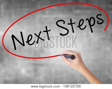Woman Hand Writing Next Steps With Black Marker Over Transparent Board
