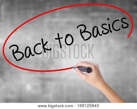 Woman Hand Writing Back To Basics Black With Marker Over Transparent Board