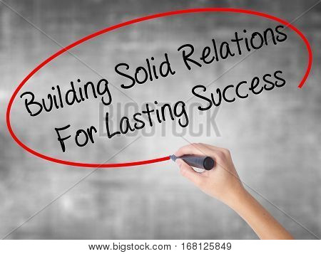 Woman Hand Writing Building Solid Relations For Lasting Success With Black Marker Over Transparent B